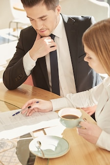Odgórny widok dwa młodego ludzie biznesu dyskutuje projekt przy sklep z kawą