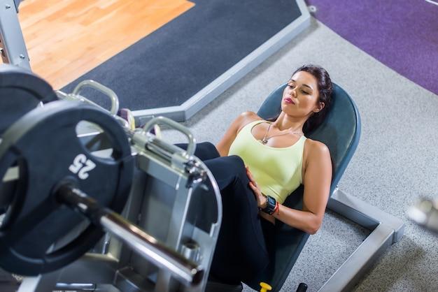 Odgórny widok dysponowana młoda kobieta robi nogi prasie w gym
