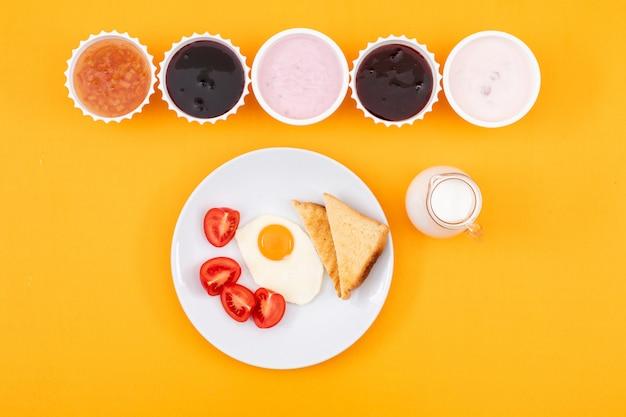 Odgórny widok dżem z jogurtem i smażącym jajkiem na kolor żółty powierzchni horyzontalnym