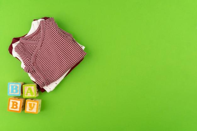 Odgórny widok dziecko odziewa na zielonym tle