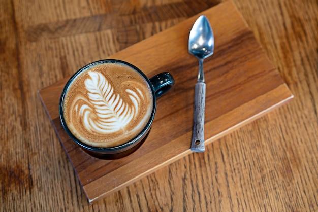 Odgórny widok filiżanka gorąca kawowa cappuccino latte sztuka z teaspoon na drewnianym talerzu.