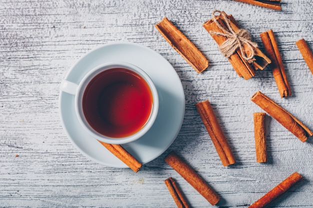 Odgórny widok filiżanka herbata z suchym cynamonem na białym drewnianym tle. poziomy