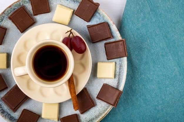 Odgórny widok filiżanka kawy z białą i ciemną czekoladą na białym drewnianym tle z kopii przestrzenią