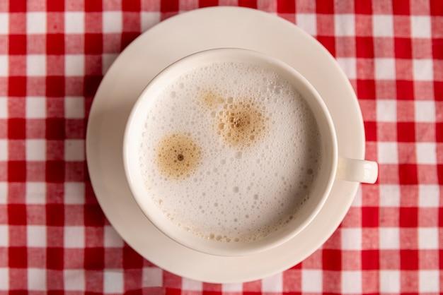 Odgórny widok filiżanka kawy z w kratkę tłem
