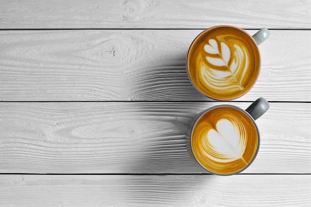 Odgórny widok filiżanki kawy latte na białym drewnianym tle