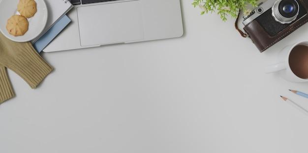 Odgórny widok fotografa wygodny workspace z biurowymi dostawami na bielu stołu tle