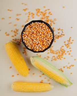 Odgórny widok garnek pełno kukurydzani ziarna i kukurudze na biel powierzchni