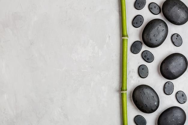 Odgórny widok gorący zdrojów kamienie ustawiający dla masażu na szarym tle