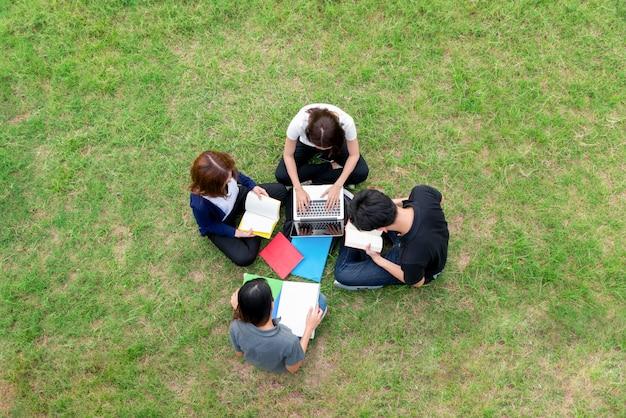Odgórny widok grupa azjatyccy ucznie siedzi wpólnie przy parkiem.