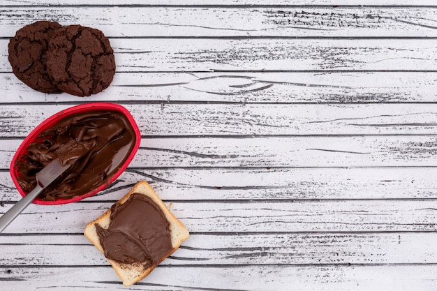 Odgórny widok grzanka z czekoladą, ciastka i kopii przestrzeń na białym drewnianym tle horyzontalnym