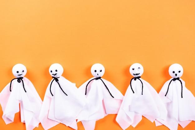 Odgórny widok halloween wykonuje ręcznie, papierowy duch na pomarańcze papieru tle z copyspace