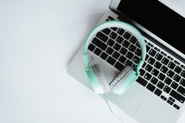 Odgórny widok hełmofony z komputerowym laptopem na białym biurowym biurku dla rozrywki i czasu wolnego online pojęcia