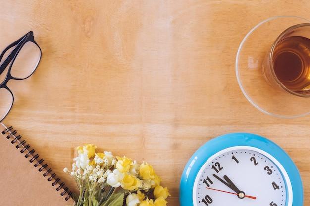 Odgórny widok herbaciana filiżanka z zegarem, kwiatem, notatnikiem i szkłami na drewnianym stole ,. wolne miejsce na tekst