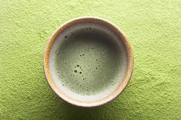 Odgórny widok herbaciany matcha w pucharze na zieleni powierzchni