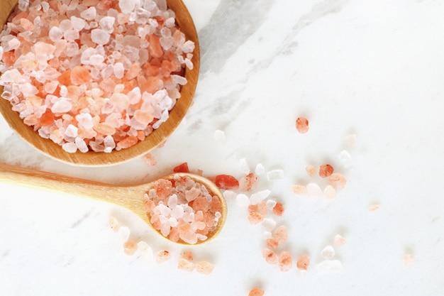 Odgórny widok himalajska różowa rockowa sól w drewnianym pucharze i łyżce na białego marmuru stole.