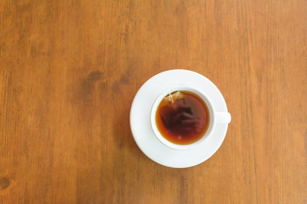 Odgórny widok i zbliżenie gorąca herbaciana filiżanka na drewnianej kopii przestrzeni i stole.
