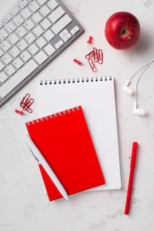 Odgórny widok jabłko na biurku z notatnikami i piórami