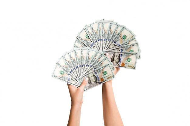 Odgórny widok kobiet ręki daje fanowi dolarowi rachunki na odosobnionym tle
