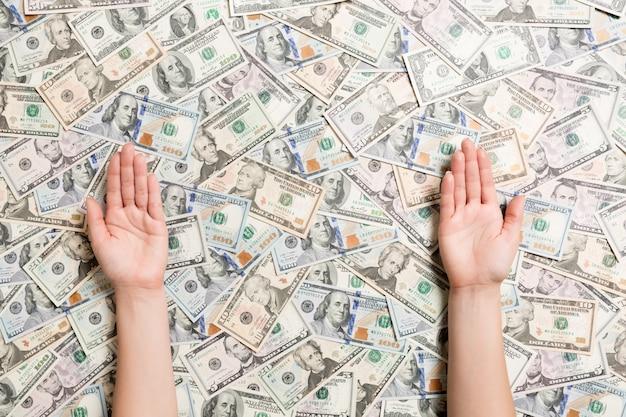 Odgórny widok kobiet ręki na różnorodnym dolarowym tle
