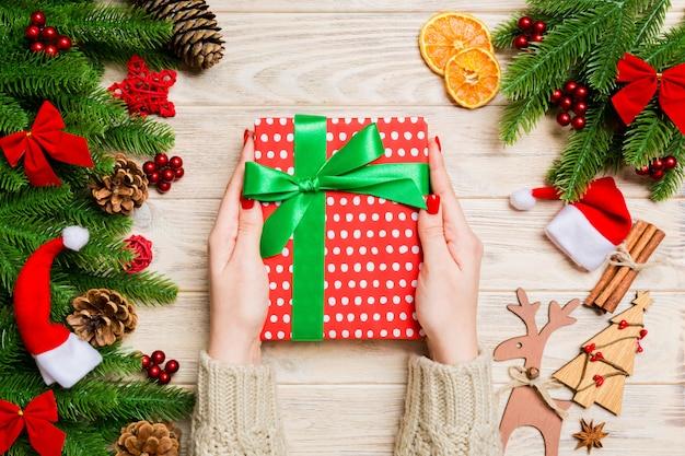 Odgórny widok kobieta trzyma prezenta pudełko w jej rękach na świąteczny drewnianym