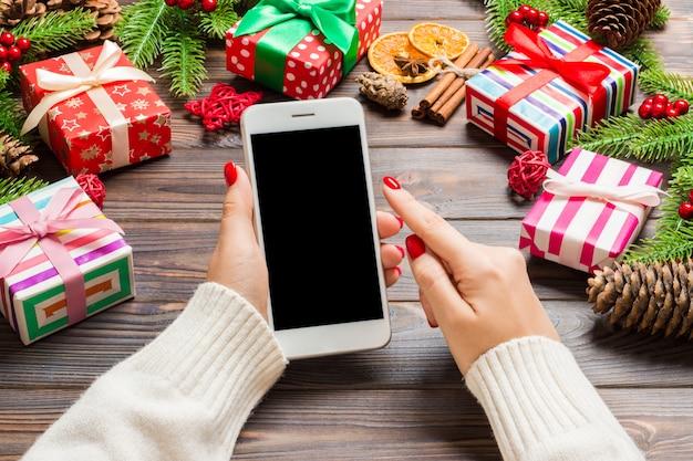 Odgórny widok kobieta trzyma telefon w jej ręce na drewnianym nowym roku robić jedlinowy drzewo i świąteczne dekoracje.