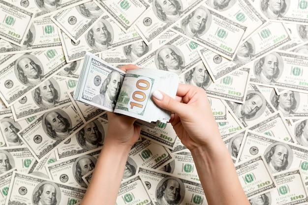 Odgórny widok kobieta wręcza odliczającego pieniądze na dolarowym tle. pojęcie długu. koncepcja inwestycji