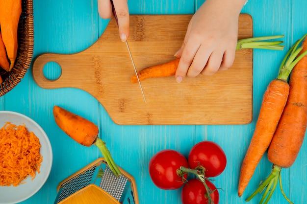 Odgórny widok kobieta wręcza tnącą marchewki na tnącej desce z nożowym pomidorem na błękitnym tle