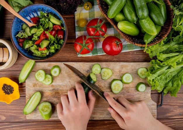 Odgórny widok kobieta wręcza tnącego ogórek z nożem na tnącej desce z jarzynowej sałatkowej sałaty pomidorowym czarnym pieprzem na drewnianej powierzchni