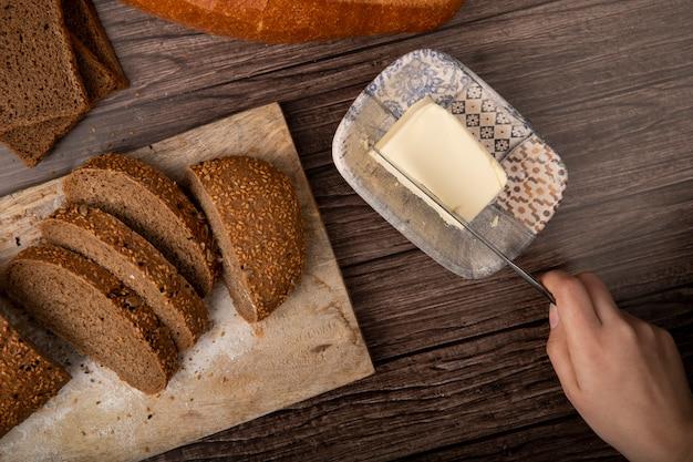 Odgórny widok kobiety ręki tnący masło z nożem i pokrojonym kanapka chlebem na tnącej desce na drewnianym tle