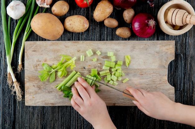 Odgórny widok kobiety ręki tnący seler na tnącej desce z warzywami i czosnku gniotownikiem na drewnianym tle
