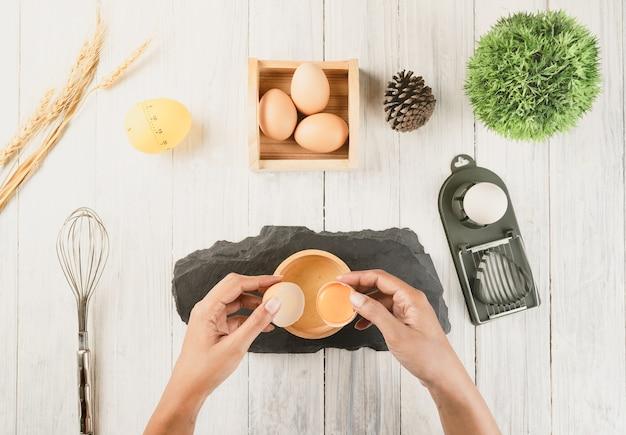 Odgórny widok kobiety szef kuchni łama jajko w drewnianego puchar. gotowanie koncepcja.