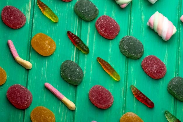 Odgórny widok kolorowi marmoladowi galaretowi cukierki na zielonym drewnie