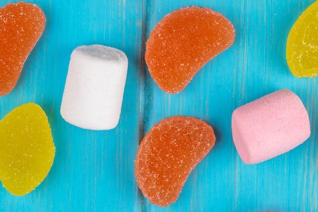 Odgórny widok kolorowi smakowici marmoladowi cukierki i marshmallows rozpraszali na błękicie