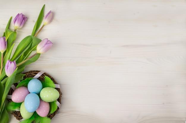 Odgórny widok kolorowi wielkanocni jajka w koszu z zielonymi piórkami i purpurowymi tulipanami na lekkim drewnianym tle z wiadomości przestrzenią.