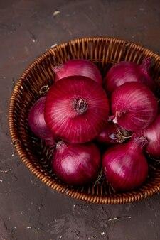 Odgórny widok kosz czerwone cebule na bordowym tle