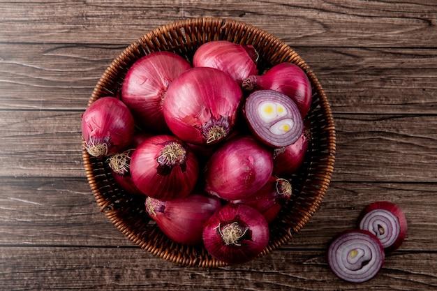 Odgórny widok kosz pełne i rżnięte czerwone cebule na drewnianym tle z kopii przestrzenią pełno