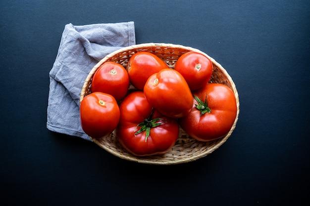 Odgórny widok kosz świezi pomidory na zmroku. koncepcja zdrowej i naturalnej żywności,