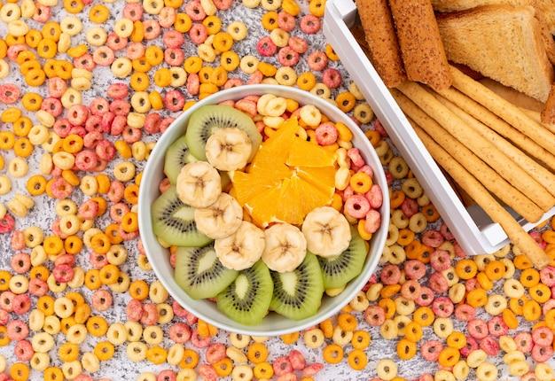 Odgórny widok krakers z kukurydzanymi pierścionkami i owoc na bielu ukazujemy się horyzontalnego