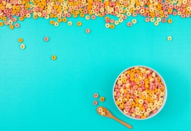Odgórny widok kukurydzani pierścionki w pucharze na błękitnym tle horyzontalnym