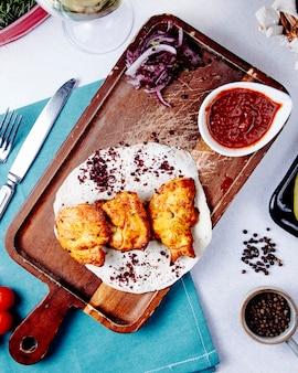 Odgórny widok kurczaka kebab z czerwonymi cebulami na drewnianej desce