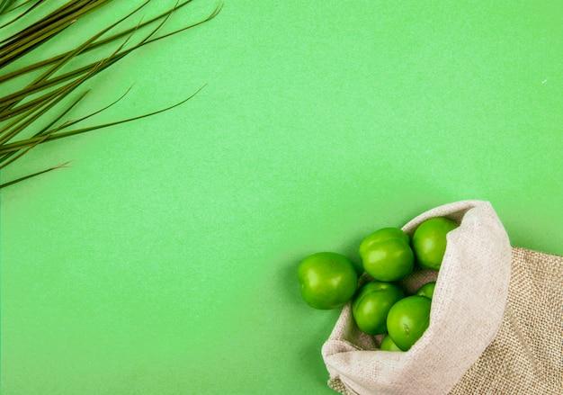 Odgórny widok kwaśne zielone śliwki rozpraszać od worka na zielonym stole z kopii przestrzenią