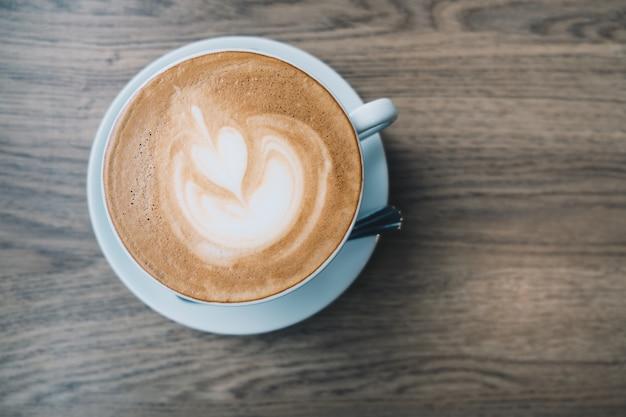Odgórny widok latte gorąca kawa w białej filiżance z latte sztuką na drewnianym stołowym tle