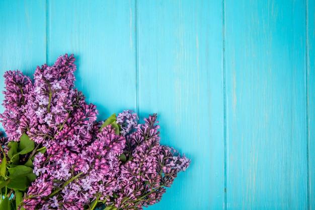 Odgórny widok lili kwiaty odizolowywający na błękitnym drewnianym tle z kopii przestrzenią