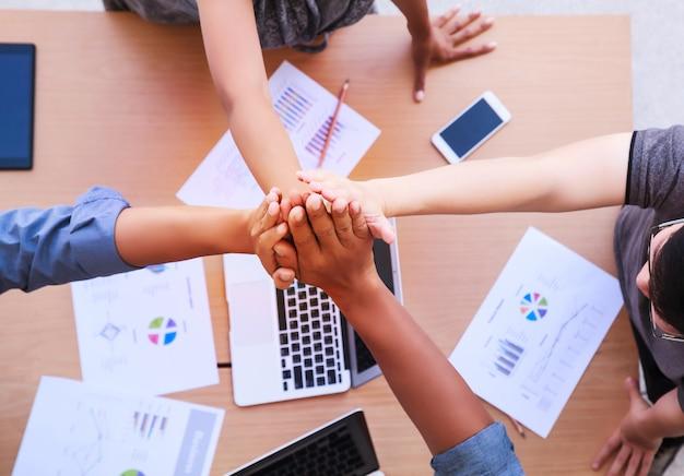 Odgórny widok ludzie biznesu broguje ręki w spotkaniu przy mobilnym biurem