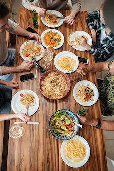 Odgórny widok ludzie je obiad wpólnie podczas gdy siedzący
