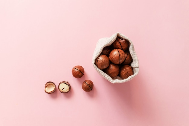 Odgórny widok macadamia dokrętki w burlap worku na różowym tle
