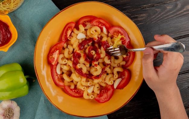 Odgórny widok makaronowy makaron w talerzu z pieprzowym ketchupu czosnkiem i ręki mienia rozwidleniem na błękitnym płótnie i drewnianej powierzchni