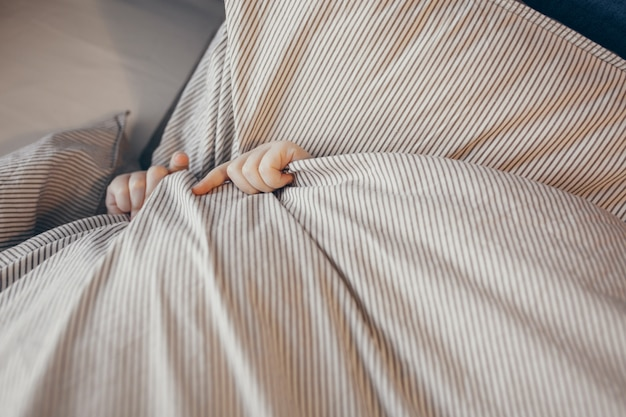 Odgórny widok mały dzieciak w łóżkowym nakryciu jego twarz z koc. ranek