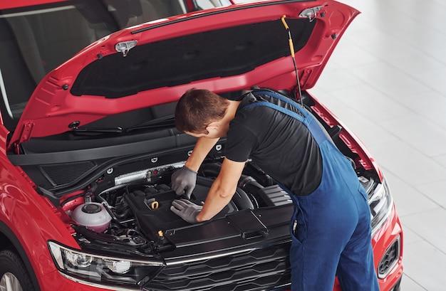 Odgórny widok męski pracownik w mundurze który naprawia czerwonego samochód