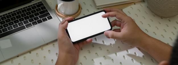 Odgórny widok męski przedsiębiorca używa horyzontalnego smartphone relaksować